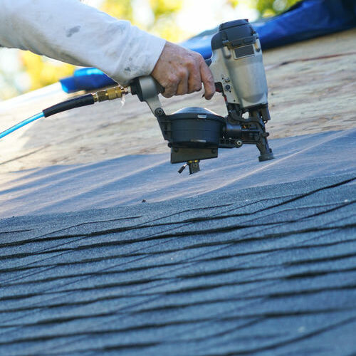 A Roofer Nails Up Roofing Shingles.